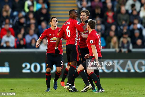 Paul Pogba of Manchester United celebrates scoring his sides first goal with team mates during the Premier League match between Swansea City and...