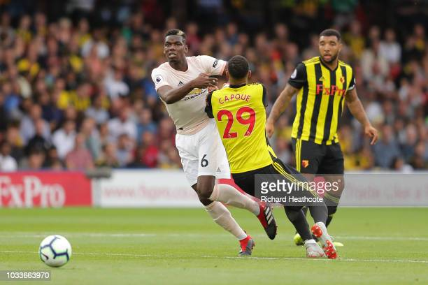 Paul Pogba of Manchester United challenges for the ball with Etienne Capoue of Watford during the Premier League match between Watford FC and...