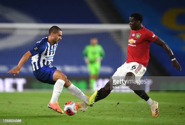 Paul Pogba of Manchester United clashes with Neal Maupay of Brighton during the Premier League match between Brighton Hove Albion and Manchester...
