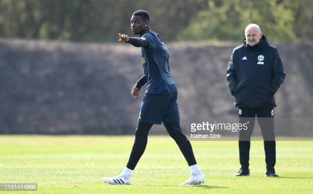 Paul Pogba of Manchester United gestures as Mike Phelan, Manchester United first team coach looks on during the Manchester United training session...