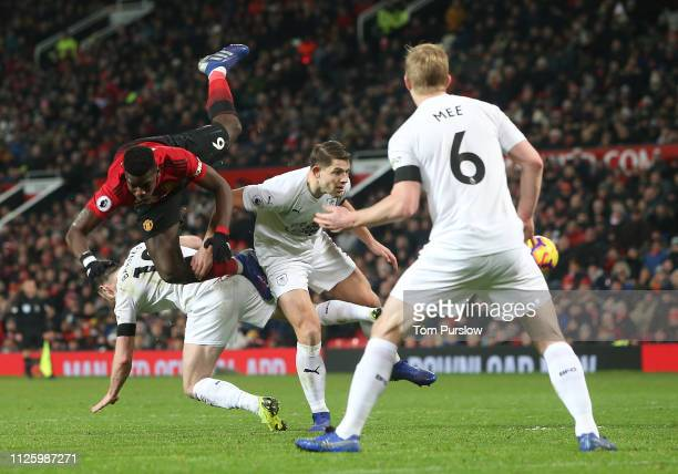 Paul Pogba of Manchester United in action with Ashley Barnes and James Tarkowski of Burnley during the Premier League match between Manchester United...