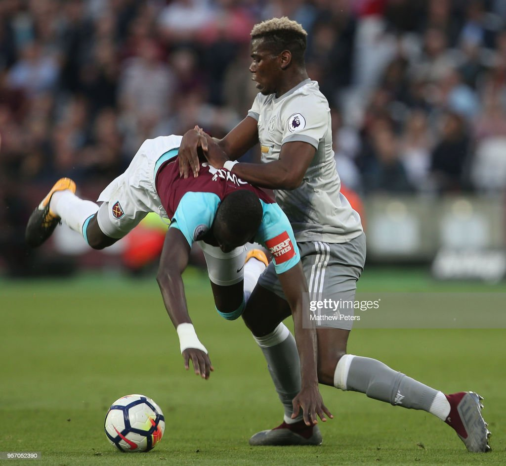 Paul Pogba of Manchester United in action with Cheikhou Kouyate of West Ham United during the Premier League match between West Ham United and Manchester United at London Stadium on May 10, 2018 in London, England.