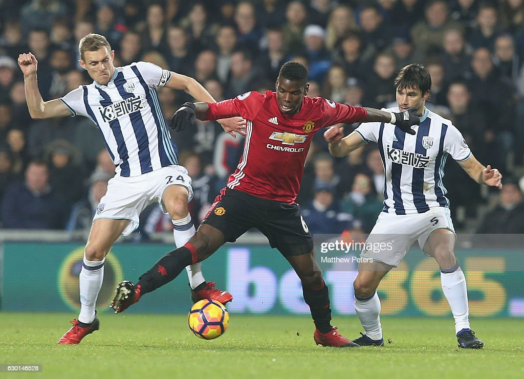 Paul Pogba of Manchester United in action with Darren Fletcher and Claudio Yacob of West Bromwich Albion during the Premier League match between West Bromwich Albion and Manchester United at The Hawthorns on December 17, 2016 in West Bromwich, England.