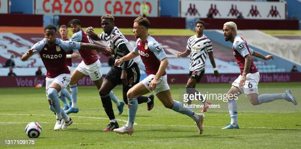 Paul Pogba of Manchester United in action with Ezri Konsa and Matty Cash of Aston Villa during the Premier League match between Aston Villa and...