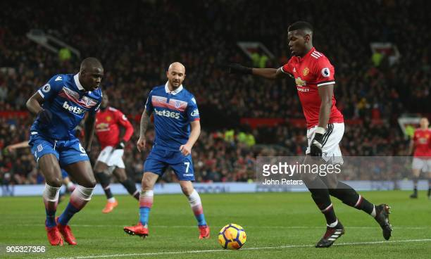 Paul Pogba of Manchester United in action with Kurt Zouma of Stoke City during the Premier League match between Manchester United and Stoke City at...