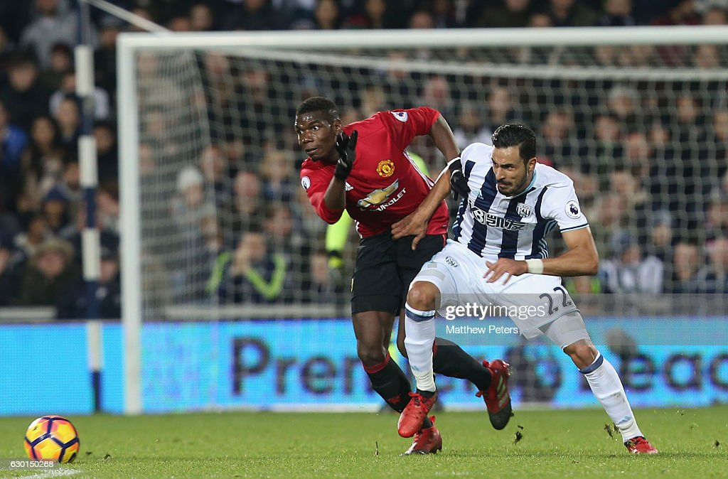 Paul Pogba of Manchester United in action with Nacer Chadli of West Bromwich Albion during the Premier League match between West Bromwich Albion and Manchester United at The Hawthorns on December 17, 2016 in West Bromwich, England.