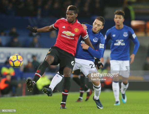 Paul Pogba of Manchester United in action with Nikola Vlasic of Everton during the Premier League match between Everton and Manchester United at...