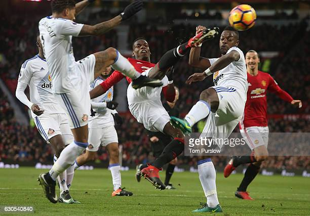 Paul Pogba of Manchester United in action with Patrick van Aanholt and Lamine Kone of Sunderland during the Premier League match between Manchester...