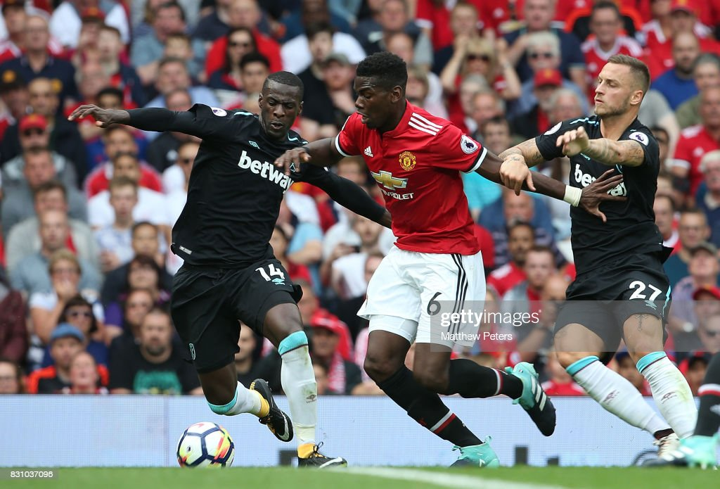 Paul Pogba of Manchester United in action with Pedro Obiang and Marko Arnautovic of West ham United during the Premier League match between Manchester United and West Ham United at Old Trafford on August 13, 2017 in Manchester, England.