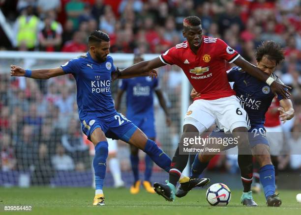 Paul Pogba of Manchester United in action with Riyad Mahrez and Shinji Okazaki of Leicester City during the Premier League match between Manchester...