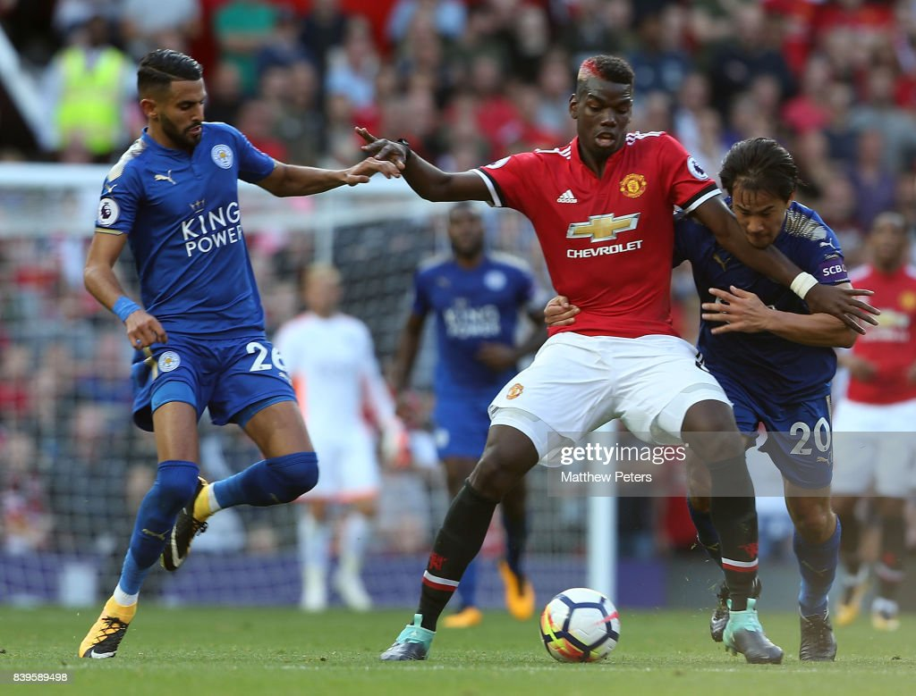 Paul Pogba of Manchester United in action with Riyad Mahrez and Shinji Okazaki of Leicester City during the Premier League match between Manchester United and Leicester City at Old Trafford on August 26, 2017 in Manchester, England.