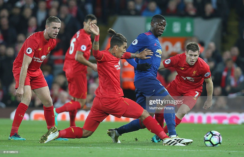 Paul Pogba of Manchester United in action with Roberto Firmino and James Milner of Liverpool during the Premier League match between Liverpool and Manchester United at Anfield on October 17, 2016 in Liverpool, England.