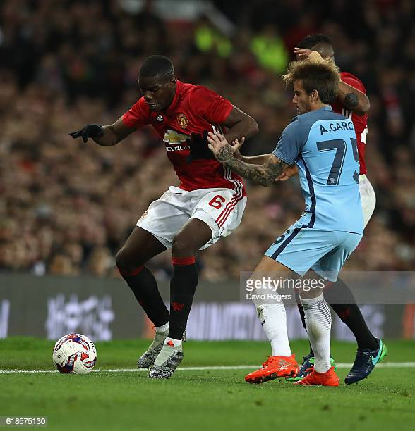 Paul Pogba of Manchester United is challenged by Aleix Garcia during the EFL Cup Fourth Round match between Manchester United and Manchester City at...