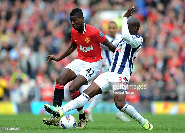 Paul Pogba of Manchester United is challenged by MarcAntoine Fortune of West Bromwich Albionduring the Barclays Premier League match between...