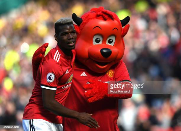Paul Pogba of Manchester United is embraced by the Manchester United mascot after the Premier League match between Manchester United and Watford at...