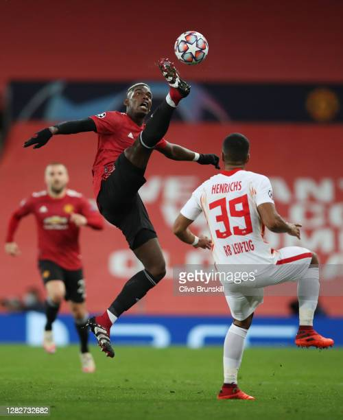 Paul Pogba of Manchester United reaches for the ball whilst under pressure from Benjamin Henrichs of RB Leipzig during the UEFA Champions League...