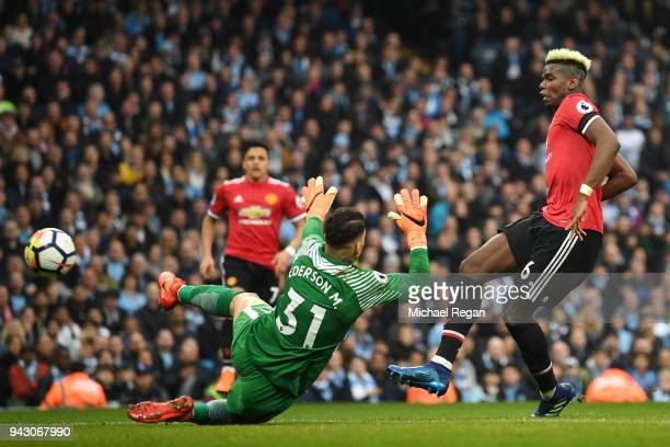 Paul Pogba of Manchester United scores his side's first goal past Ederson of Manchester City during the Premier League match between Manchester City...