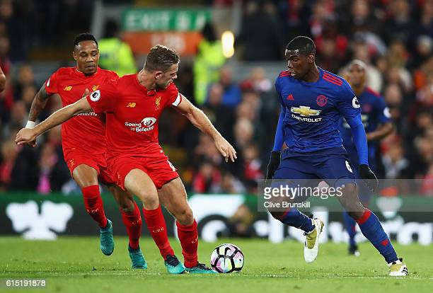 Paul Pogba of Manchester United takes on Jordan Henderson and Nathaniel Clyne of Liverpool during the Premier League match between Liverpool and...