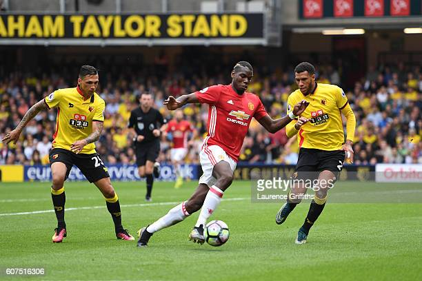 Paul Pogba of Manchester United takes the ball past Jose Holebas of Watford and Etienne Capoue of Watford during the Premier League match between...