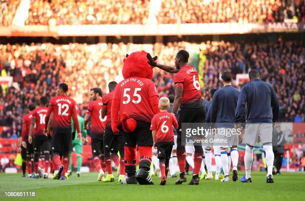 Paul Pogba of Manchester United walks out with Fred The Red and a mascot ahead of the Premier League match between Manchester United and Everton FC...