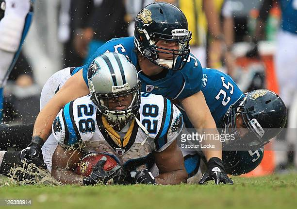 Paul Posluszny of the Jacksonville Jaguars and teammate Daryl Smith tackle Jonathan Stewart of the Carolina Panthers during their game at Bank of...