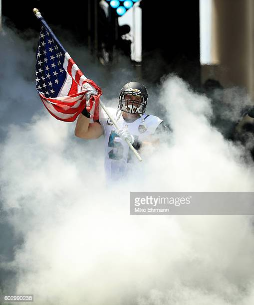 Paul Posluszny of the Jacksonville Jaguars carries the American flag during the game against the Green Bay Packers at EverBank Field on September 11...