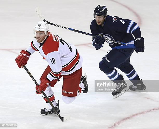 Paul Postma of the Winnipeg Jets and Bryan Bickell of the Carolina Hurricanes head to the Carolina zone during NHL action on October 22 2016 at the...