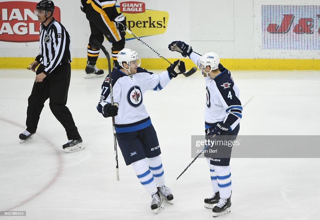 Paul Postma #4 of the Winnipeg Jets celebrates with Adam Lowry #17 after scoring a goal in the third period during the game against the Pittsburgh Penguins at PPG PAINTS Arena on February 16, 2017 in Pittsburgh, Pennsylvania.