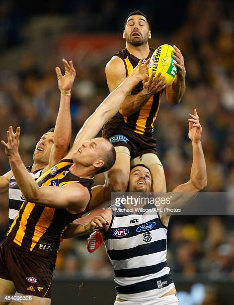 Paul Puopolo of the Hawks attempts a spectacular mark over teammate David Hale and Jared Rivers of the Cats during the 2015 AFL round 20 match...