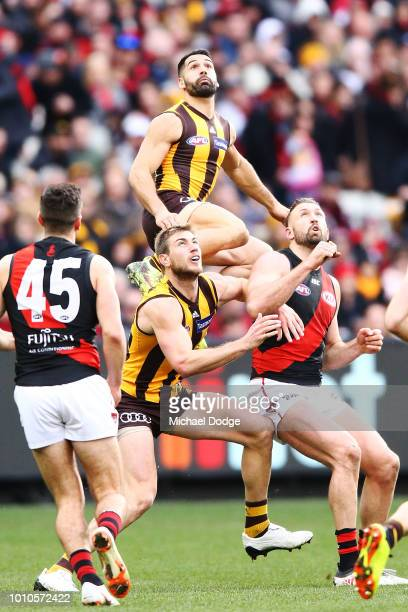 Paul Puopolo of the Hawks competes for the ball against over teammate Ryan Schoenmakers and Cale Hooker of the Bombers during the round 20 AFL match...