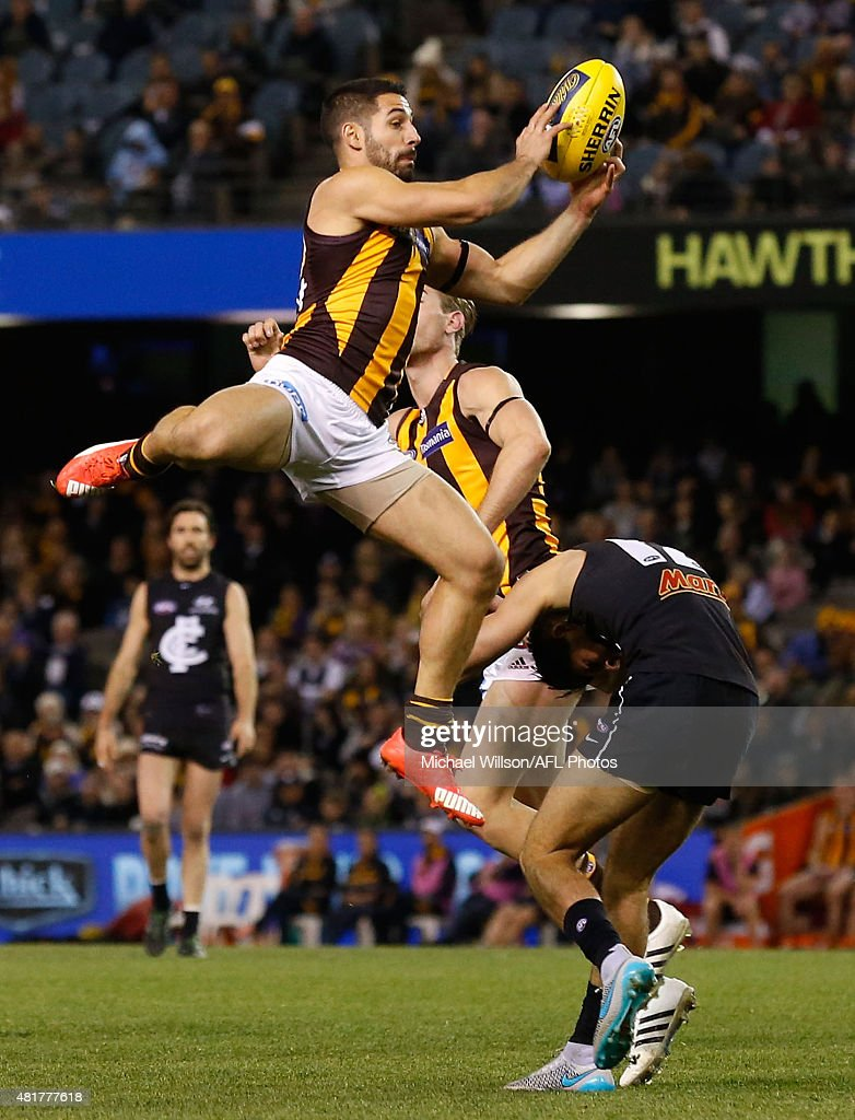 Paul Puopolo of the Hawks marks over Blaine Boekhorst of the Blues during the 2015 AFL round 17 match between the Carlton Blues and the Hawthorn Hawks at Etihad Stadium, Melbourne, Australia on July 24, 2015.