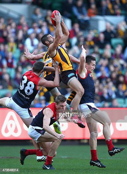 Paul Puopolo of the Hawks marks over the top of Tom McDonald and Jack Grimes of the Demons during the round seven AFL match between the Hawthorn...
