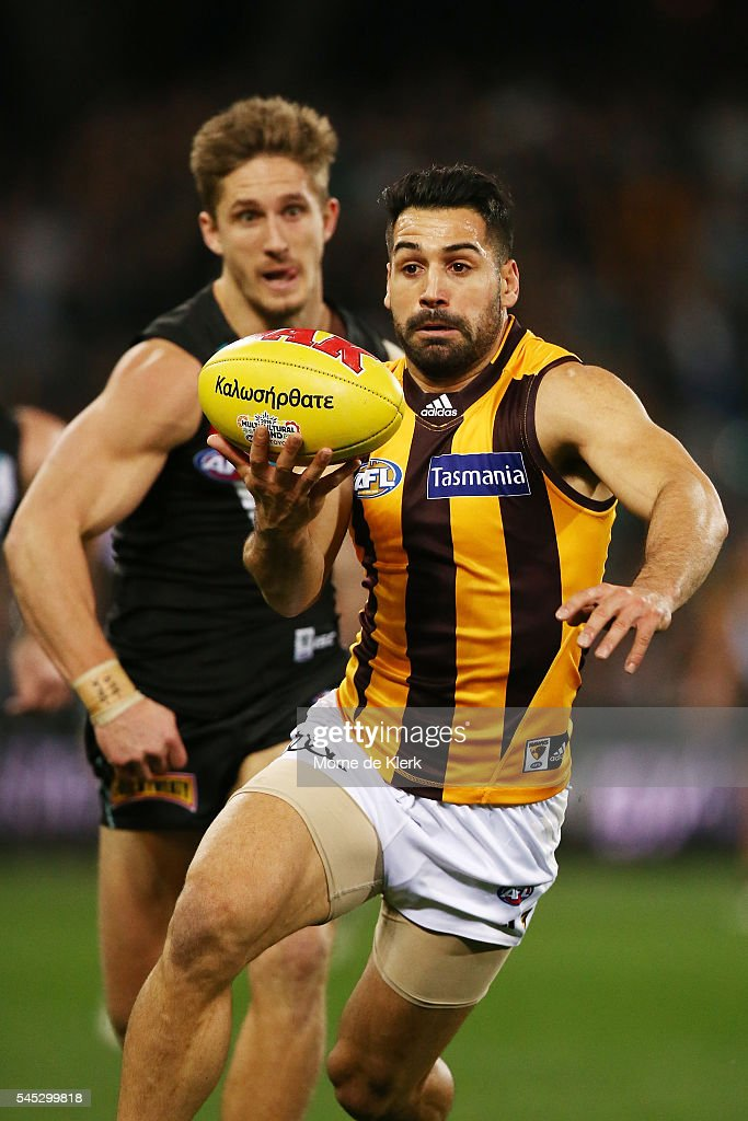 Paul Puopolo of the Hawks tries to evade Hamish Hartlett of the Power during the round 16 AFL match between the Port Adelaide Power and the Hawthorn Hawks at Adelaide Oval on July 7, 2016 in Adelaide, Australia.