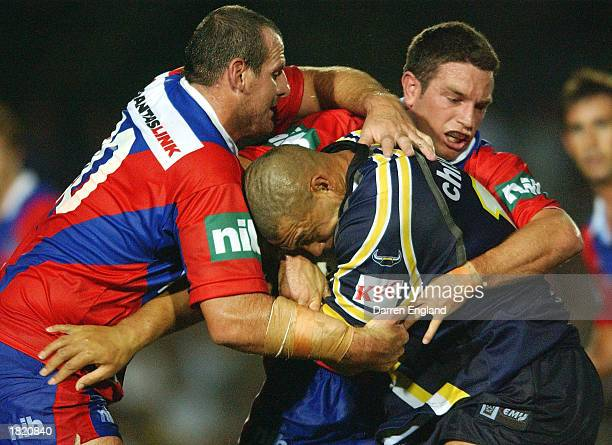 Paul Rauhihi of the Cowboys is tackled by Matt Parsons and Danny Buderus of Newcastle during the NRL trial game played between the North Queensland...