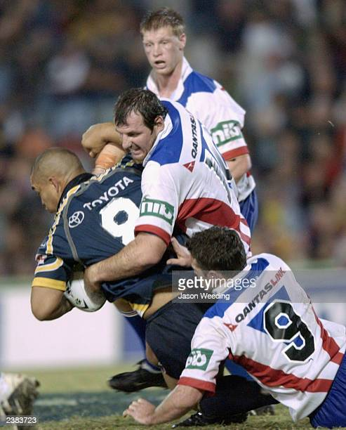Paul Rauhihi of the Cowboys is tackled during the round 22 NRL match between the North Queensland Cowboys and the Newcastle Knights at Dairy Farmers...