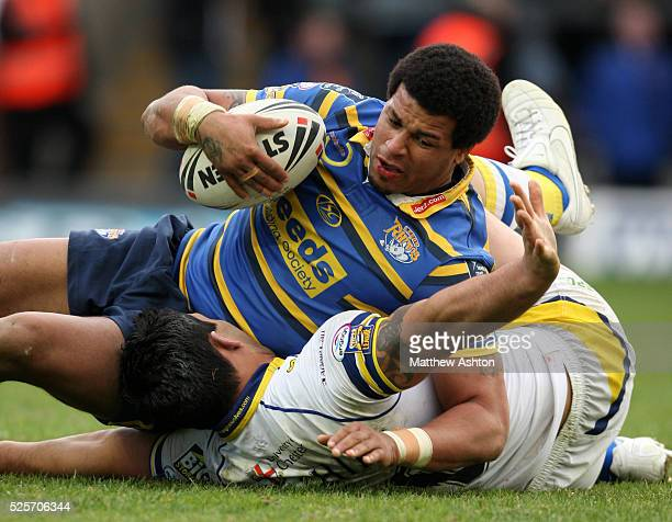 Paul Rauhihi of Warrington Wolves tries to stop Ryan Bailey of Leeds Rhinos