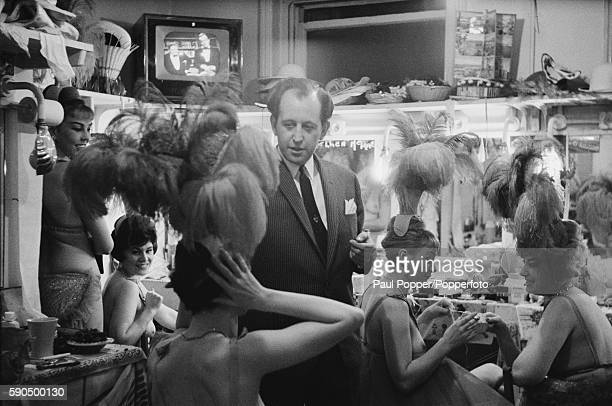 Paul Raymond producer of nude shows at his club with some of his dancers in a dressing room backstage at the Raymond Revuebar in Soho London December...