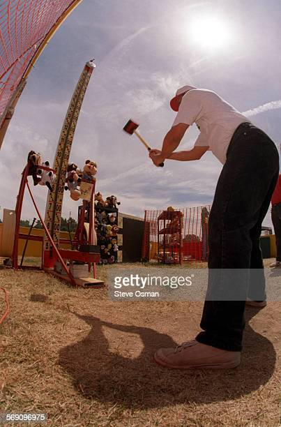 Paul Regina swings a sledge hammer at the Conejo Valley Rotary's 'High Striker' booth Regina the Public Relations Director with the Suns minor league...