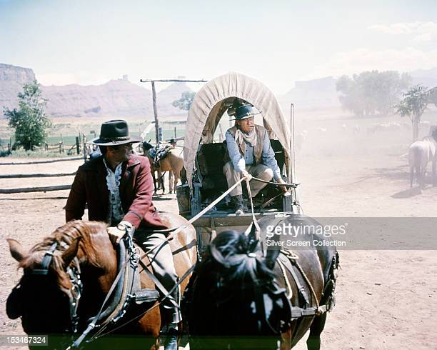 Paul Regret played by American actor Stuart Whitman and Captain Jake Cutter played by John Wayne driving a covered wagon in 'The Comancheros'...