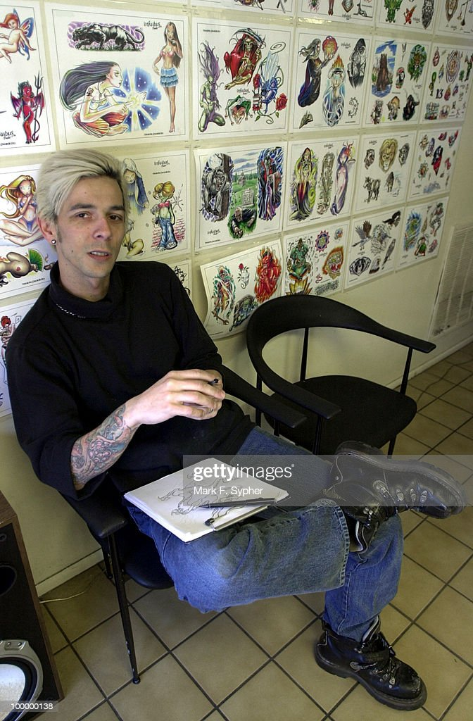Paul Roe, of Black Enque Tattoo Studio on 8th Street SE, works on a custom tattoo for a client amongst sheets of 'flash,' or pre-drawn tattoos. With summer just around the corner, Roe and his fellow artists are predicting a rise in business to accompany the rise in temperature.