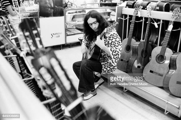 Paul Rogers playing guitar at an instrument store April 1970