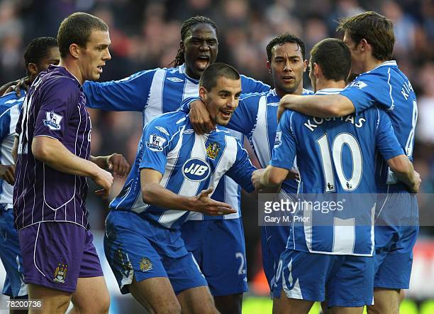 Paul Scharner of Wigan Athletic celebrates with his team mates after scoring an equalising goal during the Barclays Premier League match between...