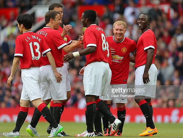 Paul Scholes and Andrew Cole of Manchester United Legends laugh as they celebrate with Louis Saha after the first goal during the Manchester United...