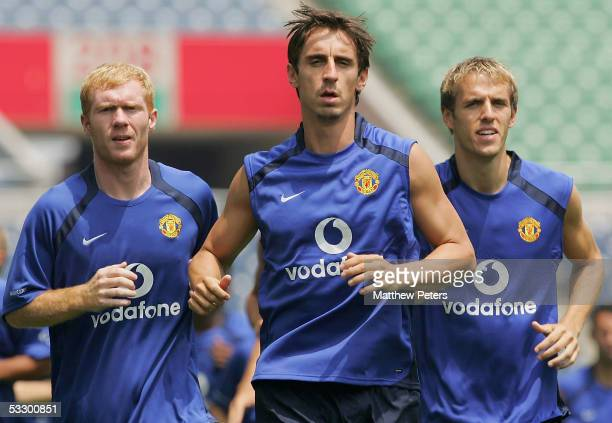 Paul Scholes, Gary Neville and Phil Neville of Manchester United in action during a first team training session at Saitama Stadium July 29, 2005 in...