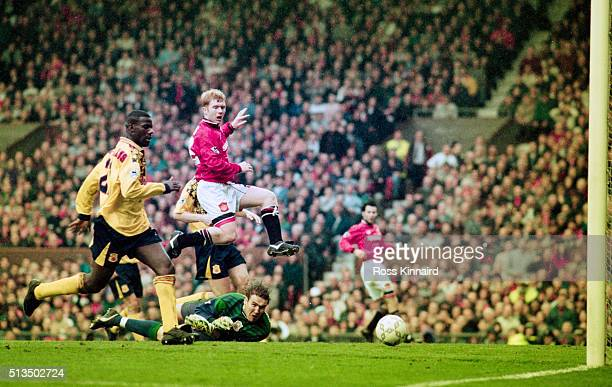 Paul Scholes of Manchester United leaps over Notts Forest goalkeeper Mark Crossley as Chris Bart Williams looks on as a shot from Ryan Giggs goes...