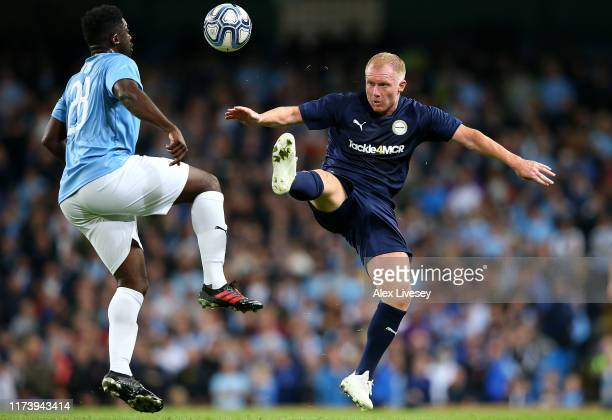 Paul Scholes of Premier League All-Starts XI tackles Kolo Toure of Manchester City Legends during the Vincent Kompany testimonial match between...