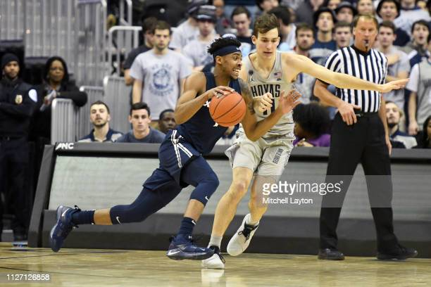 Paul Scruggs of the Xavier Musketeers dribbles by Greg Malinowski of the Georgetown Hoyas during a college basketball game at the Capital One Arena...