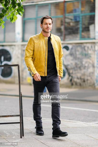 Paul Sculfor wears a yellow leather jacket a black top gray denim pants shoes during London Fashion Week Men's June 2019 on June 09 2019 in London...