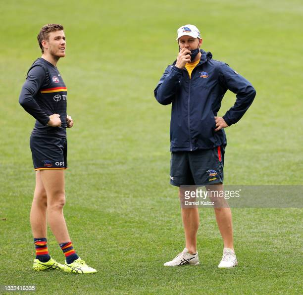 Paul Seedsman of the Crows talks with Matthew Nicks, head coach of the Crows during an Adelaide Crows AFL training session at Adelaide Oval on August...