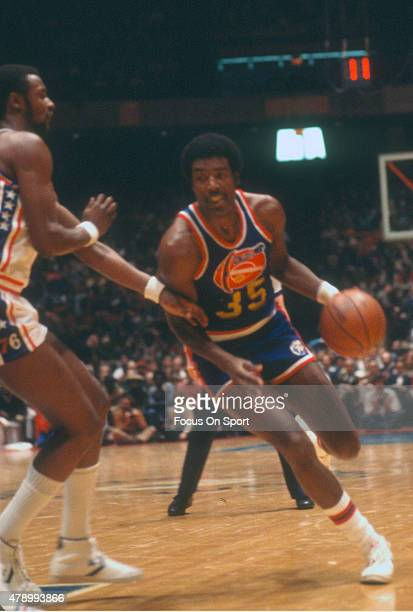 Paul Silas of the Denver Nuggets drives on Joe Bryant of the Philadelphia 76ers during an NBA basketball game circa 1977 at The Spectrum in...